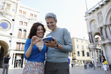 couple in the street in the middle of leisure travel planning for vacation to Italy