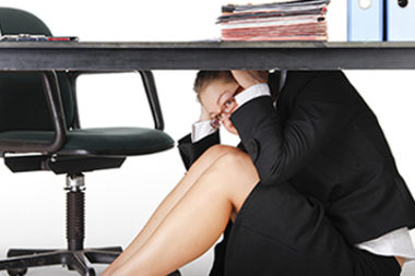 Business woman hiding under desk